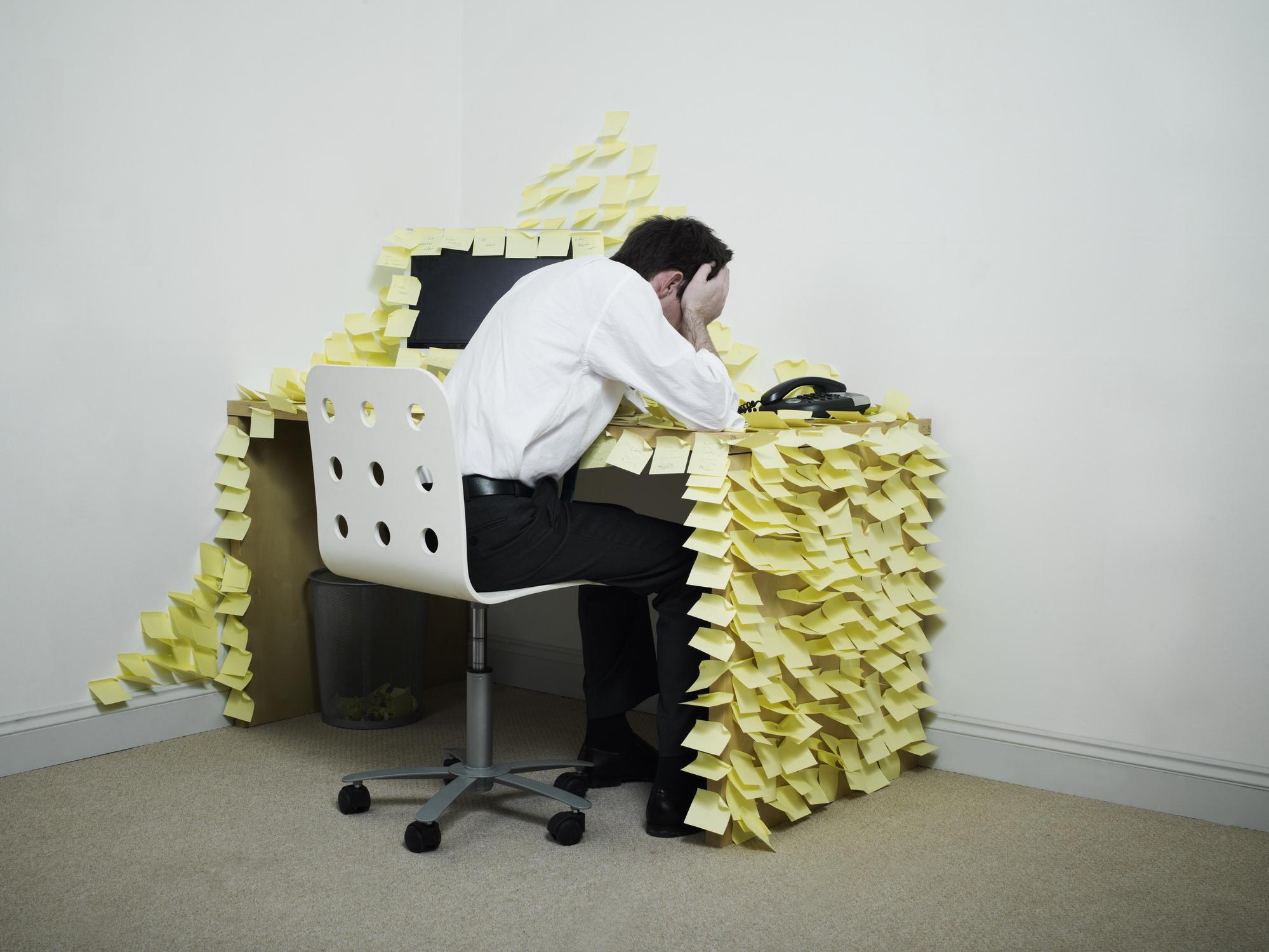Imagem de trabalhador estressado com mensagens em sua mesa