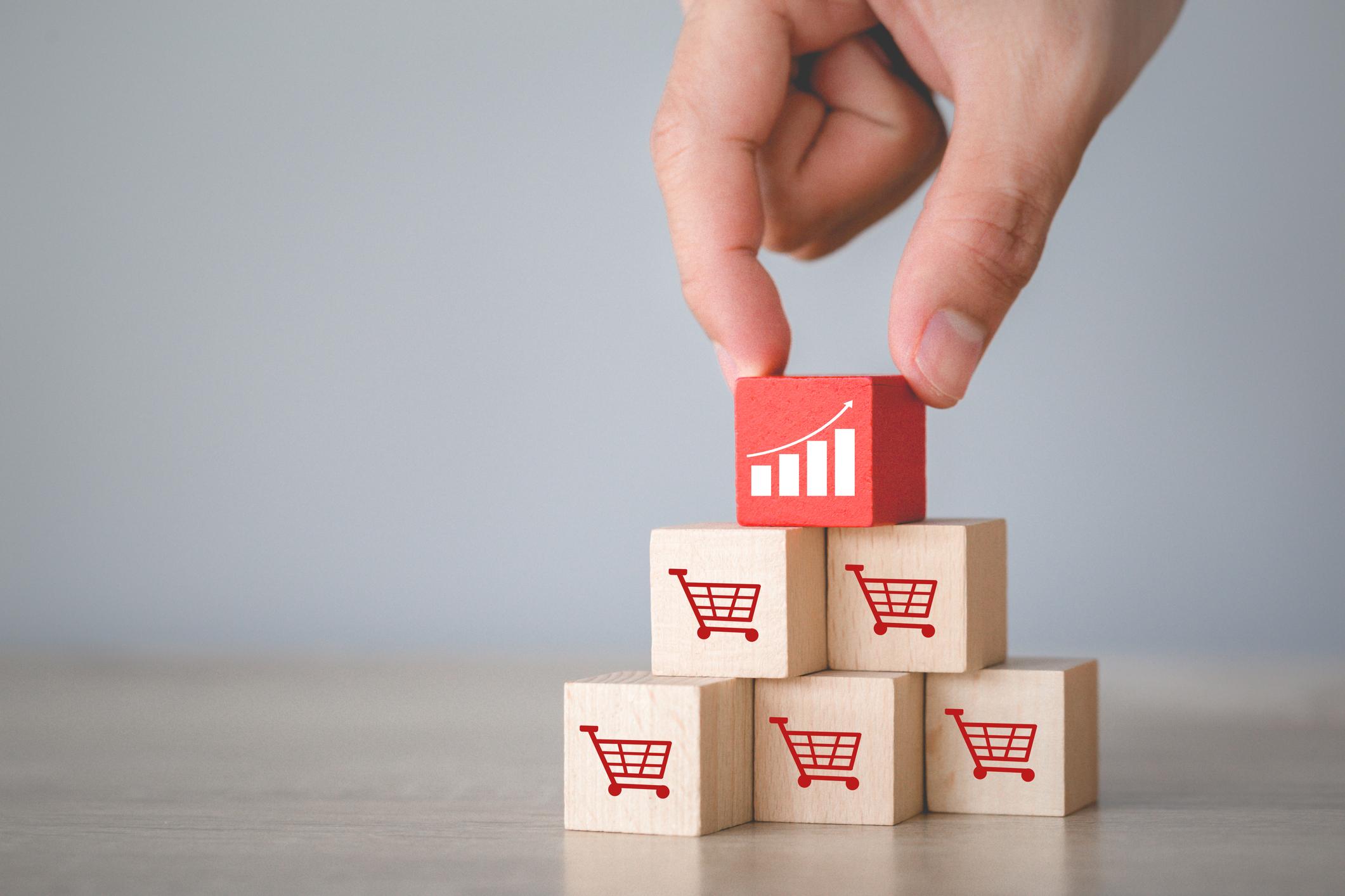 Imagem de carrinhos de compra em cubos de madeira representando aumento de vendas