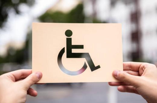 Mãos segurando papel com o símbolo de pessoa com deficiência.
