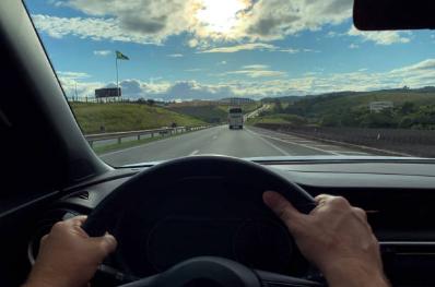 Motorista na direção de ônibus em rodovia