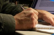 Detalhe de homem fazendo anotações em caderno com notebook ao fundo