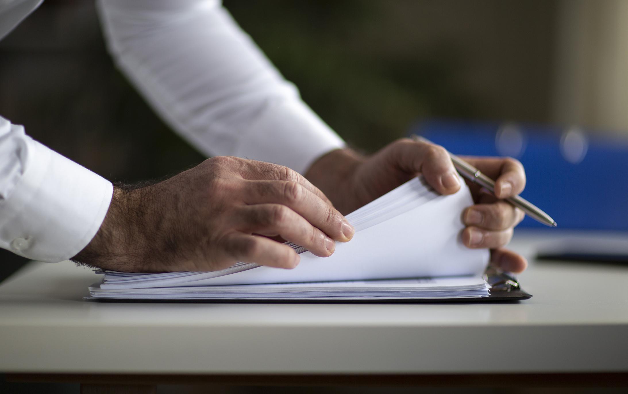 Detalhe de mãos de pessoa em roupas formais manuseando documentos com caneta