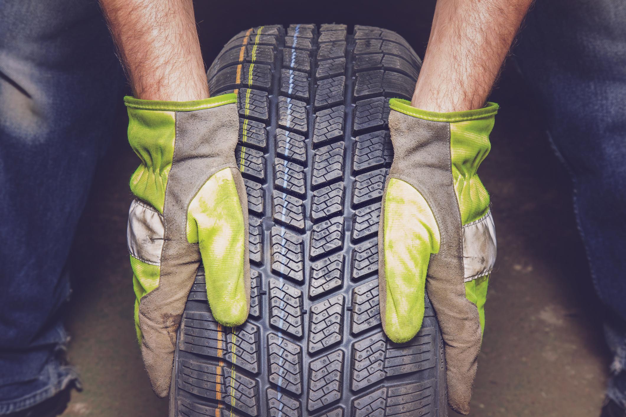 Detalhe de mãos com luvas segurando pneu
