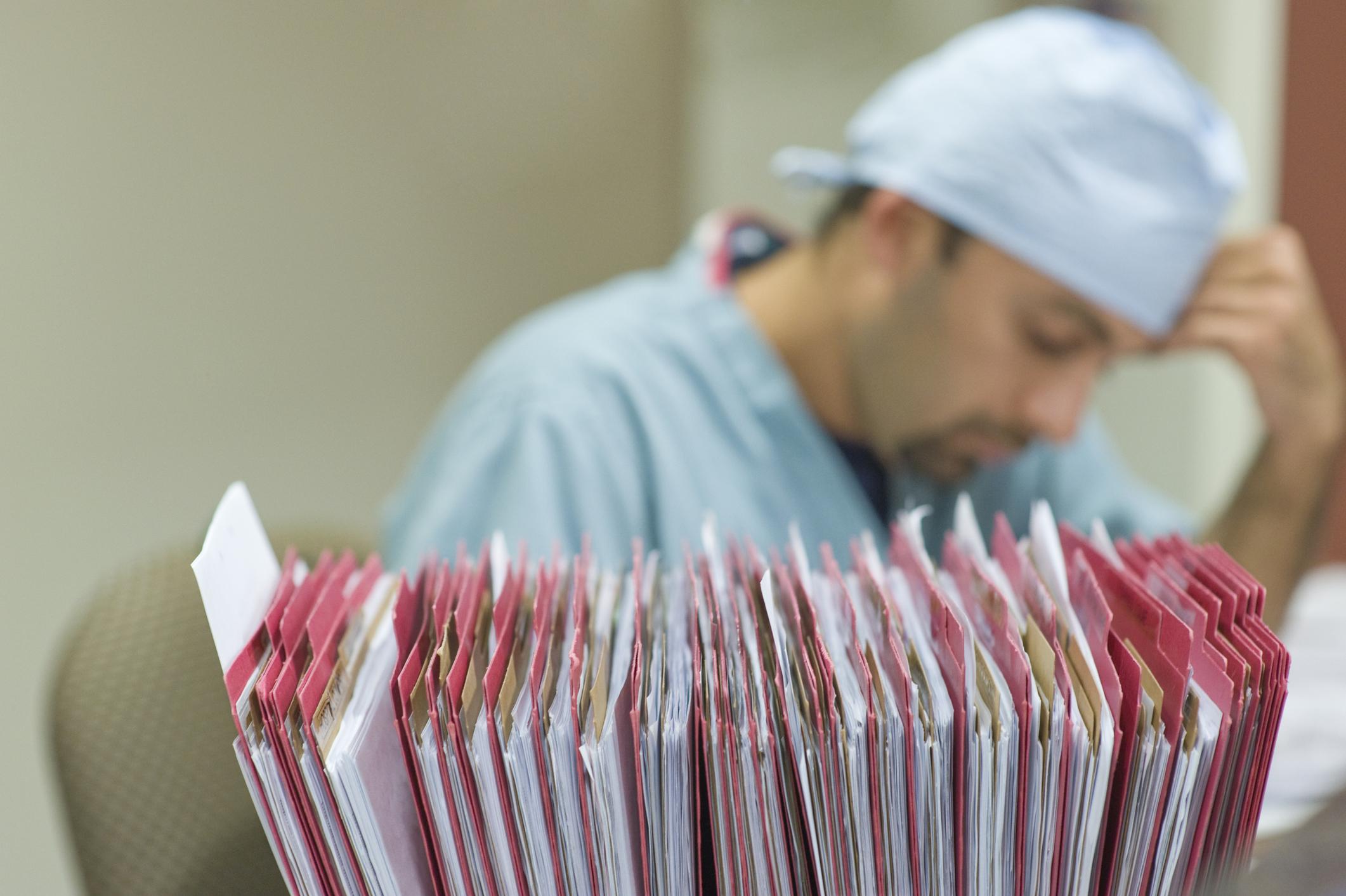 Técnico de enfermagem com prontuários médicos em primeiro plano