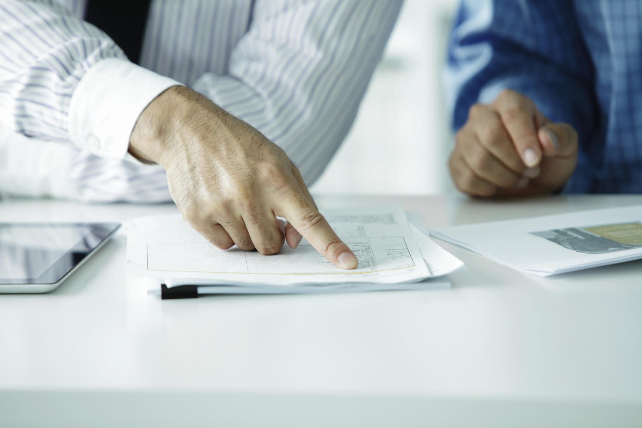 Detalhe de dois homens conferindo documentos