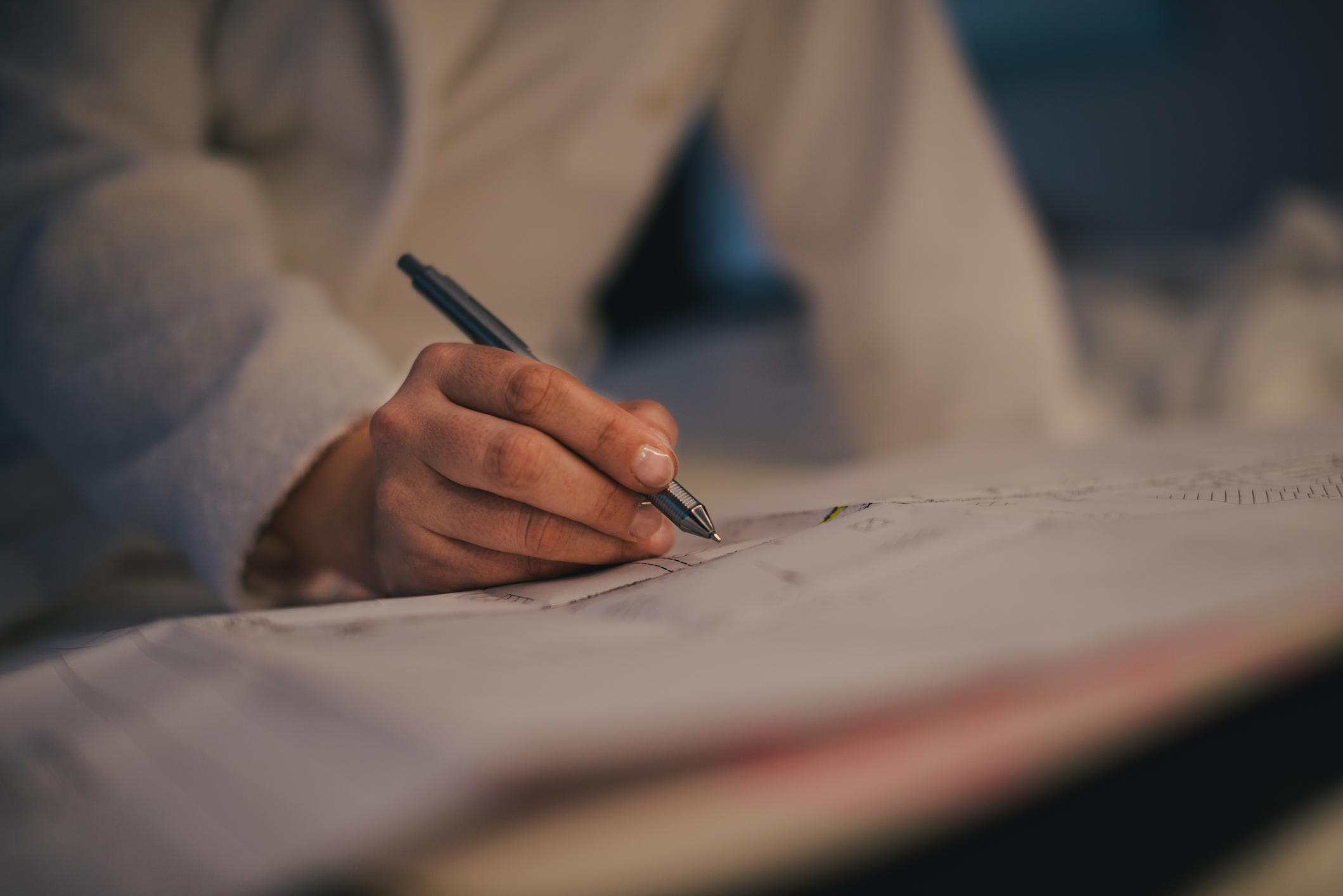 Detalhe de homem assinando documento