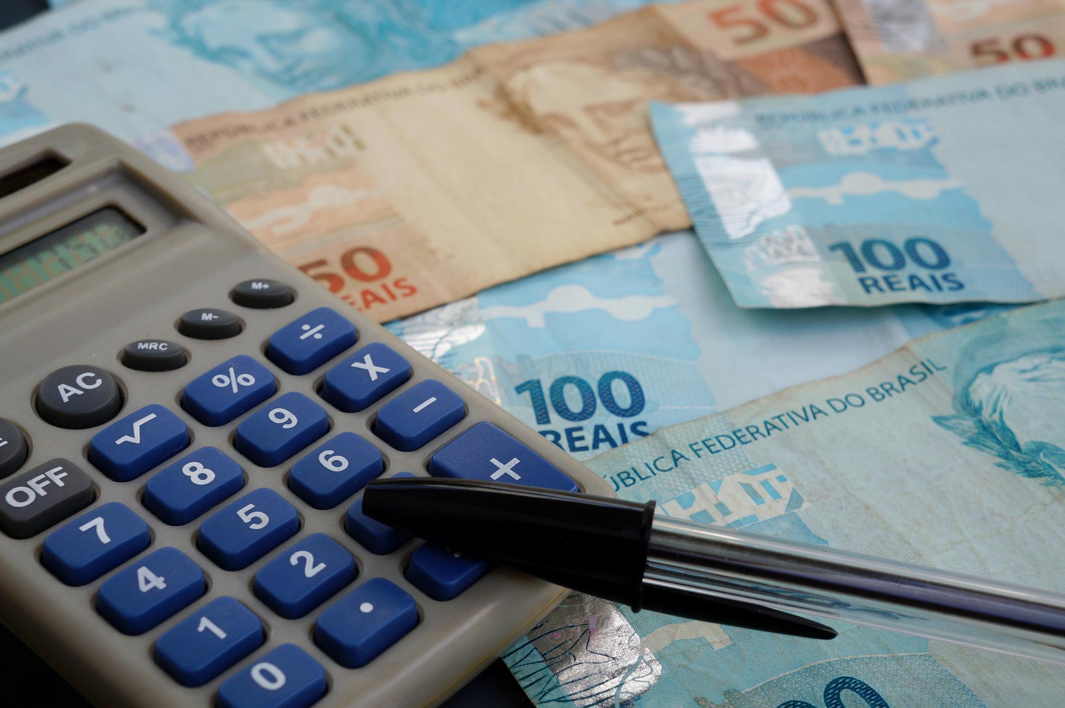 Dinheiro com calculadora e caneta