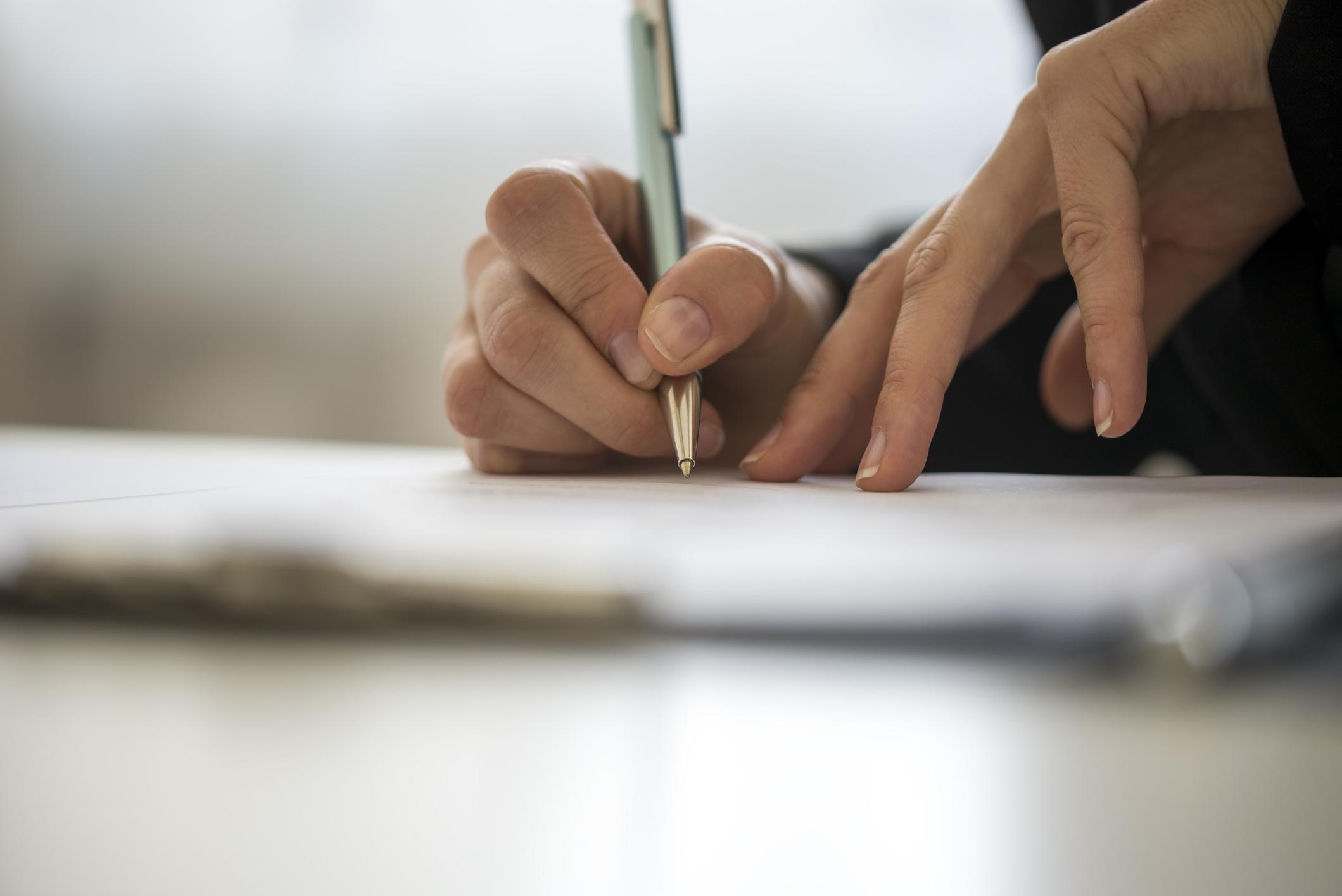 Detalhe de mão feminina assinando documento